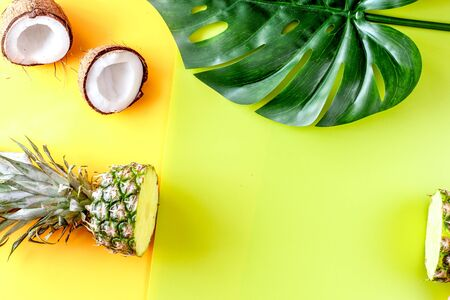 tropical fruits in hand for summer design on yellow background top view mock-up Zdjęcie Seryjne - 131754520