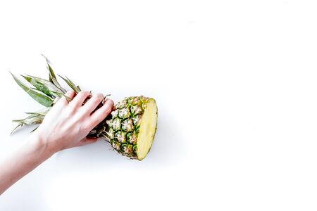 summer dessert with pineapples in hand on white table background top view mock up