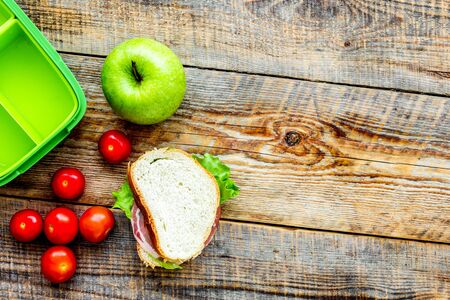 healthy break with apple, grape and sandwich in green lunchbox on home wooden table background flat lay mock-up Reklamní fotografie