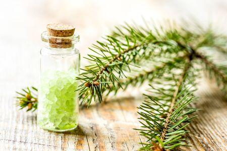 Sal de abeto cosmético en botellas con ramas de piel sobre fondo de mesa de madera Foto de archivo