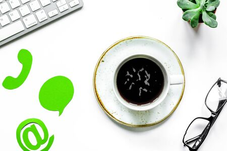 customer support company office with contact us sign and coffee on white desk background top view