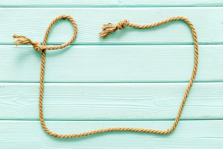 rope frame on mint green wooden background top view mock-up Stock Photo