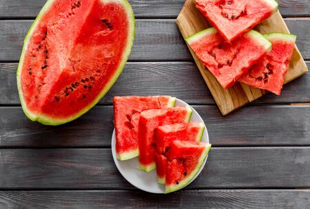 Tropical fruit. Pieces of watermelon on wooden background top view.