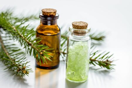 cosmetic spruce oil and salt in bottles with fur branches for aromatherapy on white table background