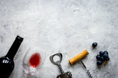 bottle of red wine and corkscrew on stone background top view mockup