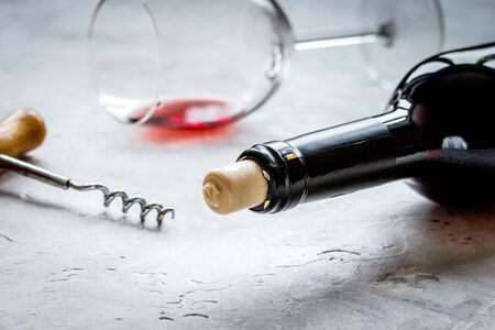 Bottle of red wine with corkscrew on white stone background 스톡 콘텐츠