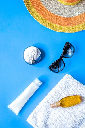 Towel, sun lotion, glasses for summer rest on blue background top view space for text