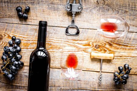 Glasses of red wine and bottle on wooden background top view
