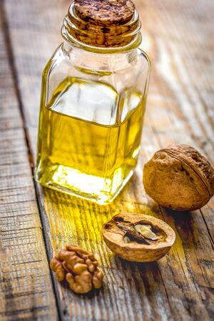 cosmetic and therapeutic walnut oil on wooden background. Reklamní fotografie
