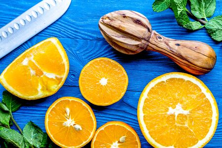 cut oranges with knife and mint leaves on blue kitchen top view