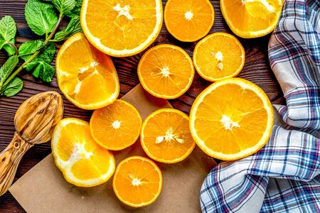 Fresh oranges in slices with mint leaves for cooking homemade juice on kitchen table top view