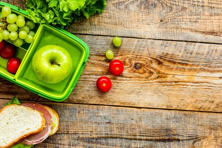 school lunch set with apple and vegetables in lunchbox background top view mock up 写真素材