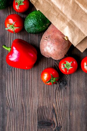 Store concept with vegetables and paper bag on wooden table background top view mockup