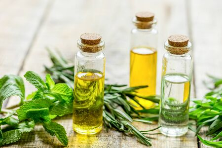 organic cosmetic oil in bottle with herbs on light wooden table background
