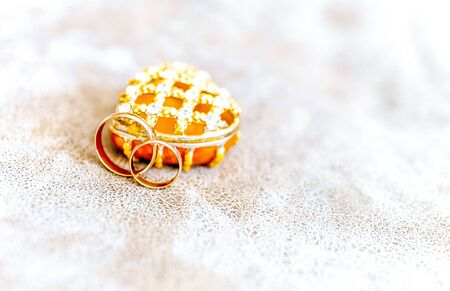 Photo of golden wedding rings before ceremony with box like heart