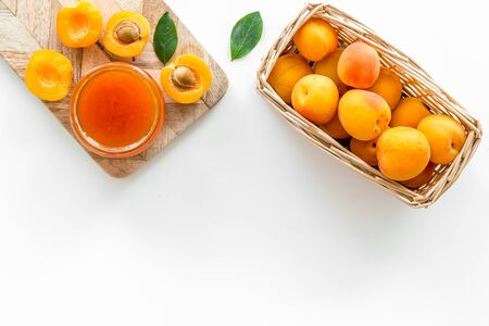 Healthy breakfast. Apricot jam in jar near fresh fruits on white background top view frame space for text