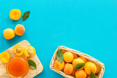 Healthy breakfast. Apricot jam in jar near fresh fruits on blue background top view frame space for text 版權商用圖片