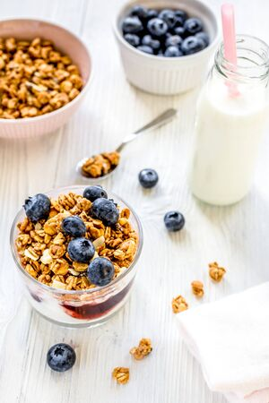 Fitness breakfast with homemade granola from yoghurt and flakes, milk and berries on white desk background Zdjęcie Seryjne