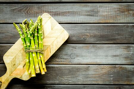 Cooking asparagus. Bunch steams on cutting board on dark wooden background top-down copy space