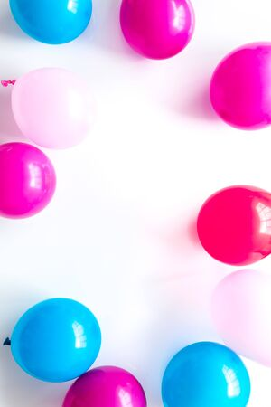 Colorful balloons frame on white background top-down.