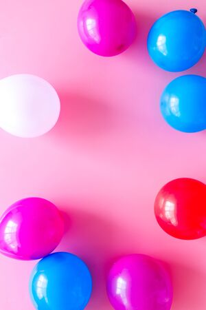 Decorative frame with colorful balloons on pink background top-down.