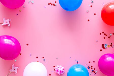 Party concept. Colorful balloons and confetti on pink background top-down.