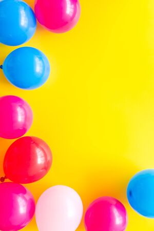 Colorful balloons frame on yellow background top-down. Фото со стока