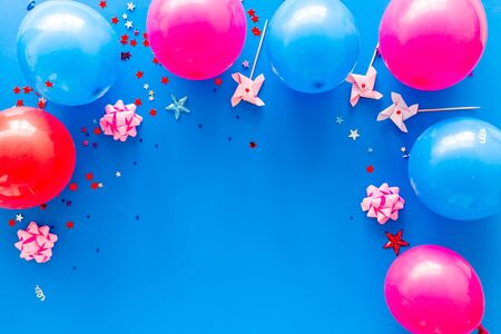 Party concept. Colorful balloons and confetti on blue background top-down.