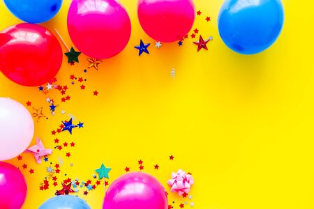 Decorative frame with colorful balloons on yellow background top-down. Фото со стока