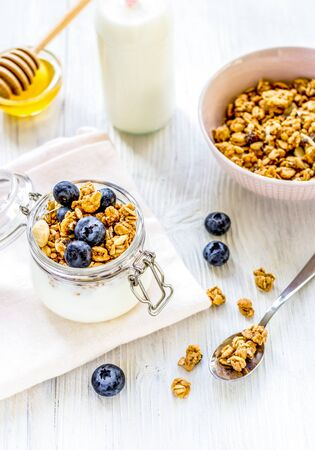 Homemade fitness granola with blueberries in jar on white kitchen table background Reklamní fotografie