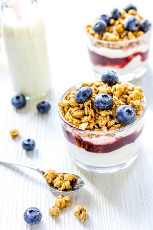 Fitness breakfast at home with muesli, honey and bottle of milk on white table background