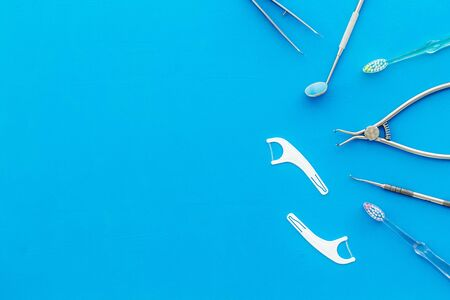 Dental care concept. Stomatological tools frame - with floss - on blue background top-down frame copy space