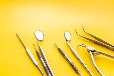 Dental instruments - set with mirrors - on yellow background close up copy space Stok Fotoğraf