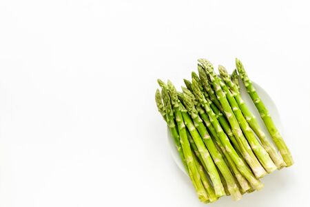 Fresh asparagus on plate on white Stock fotó