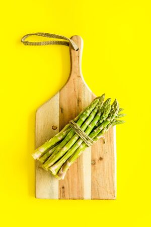 Cooking asparagus. Bunch steams on cutting board on yellow background top-down.