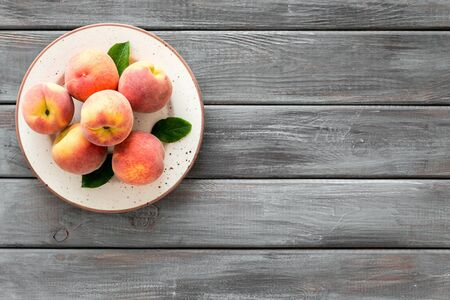 Summer fruits. Ripe red peaches on plate on dark wooden table top-down copy space