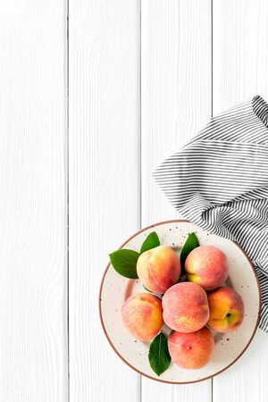 Summer lunch. Red peaches on white wooden background with tablecloth and leaves top-down copy space
