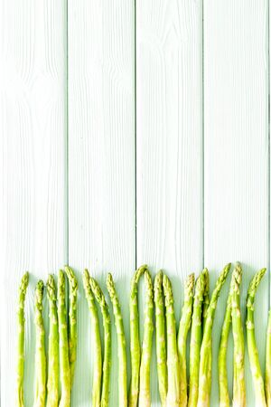 Asparagus steams frame on white wooden background top-down copy space Archivio Fotografico