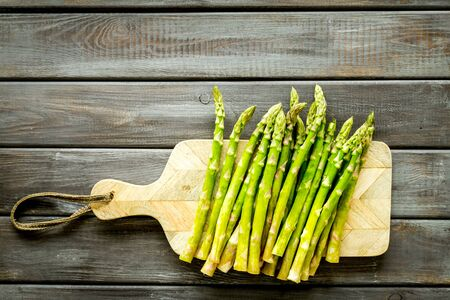 Cooking asparagus. Fresh steams on cutting board on dark wooden background top-down copy space