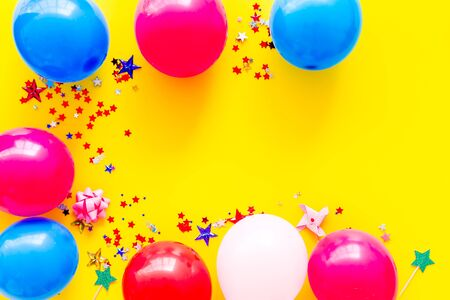 Party concept. Colorful balloons and confetti on yellow background top-down frame copy space