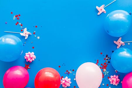 Party concept. Colorful balloons and confetti on blue background top-down frame copy space
