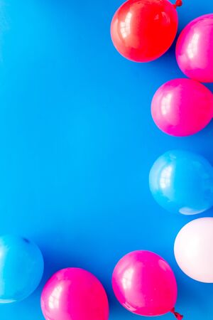 Decorative frame with colorful balloons on blue background top-down frame copy space