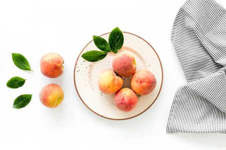Summer lunch. Red peaches on white background with tablecloth and leaves top-down