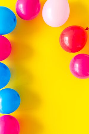 Colorful balloons frame on yellow background top-down. 写真素材
