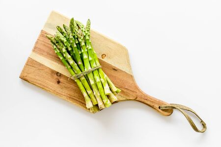 Cooking asparagus. Bunch steams on cutting board on white background top-down copy space