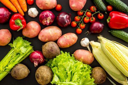 Fresh vegetables still life. Potato, cucumber, beet carrot, greenery on black background top-down Фото со стока