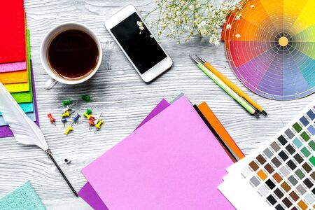 profession concept with graphic designer tools, cup of coffee and mobile on wooden work desk background top view