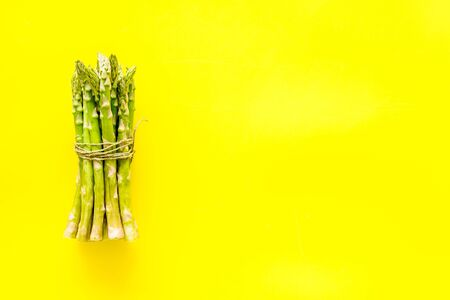 Bunch of asparagus steams on yellow background top-down copy space Archivio Fotografico
