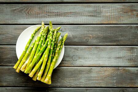 Fresh asparagus on plate on dark wooden Archivio Fotografico