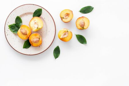 Healthy food. Ripe sliced peaches on plate on white table top-down copy space